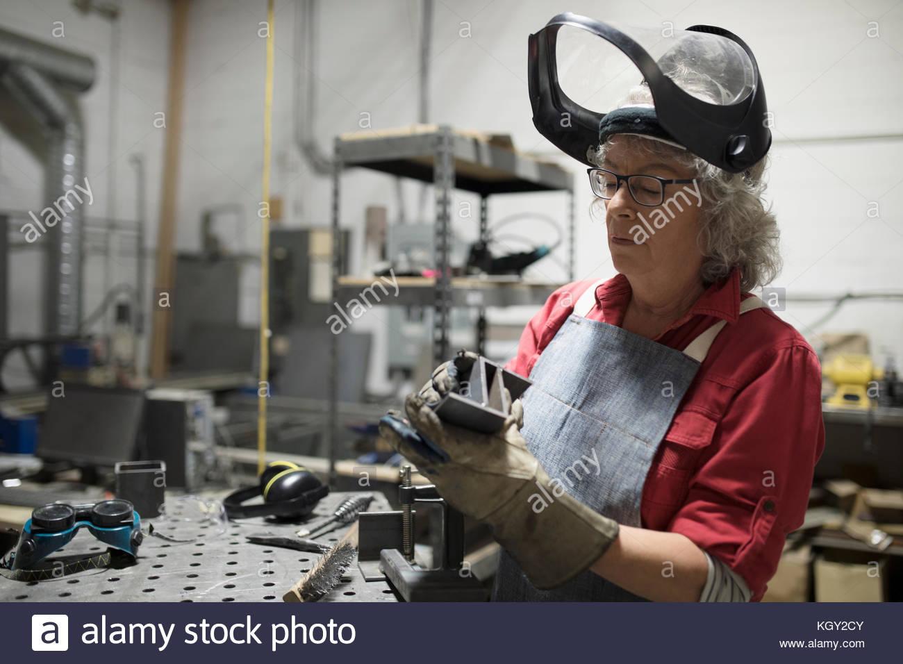 L'examen de soudeur féminine senior pièce en acier à l'atelier Photo Stock