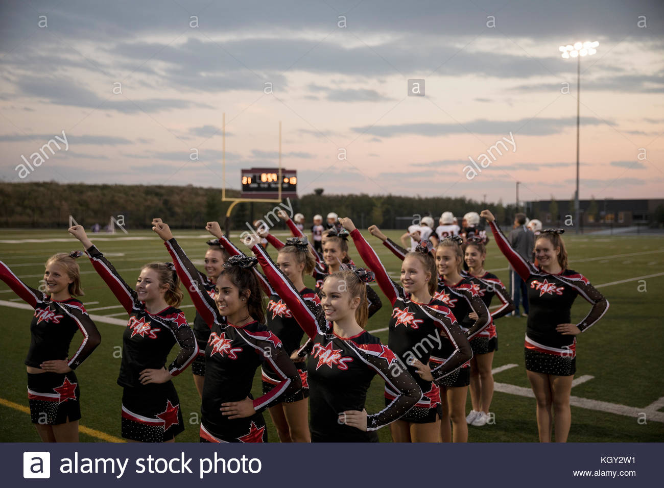 Teenage girl high school cheerleaders de marge de jeu sur terrain de football Photo Stock