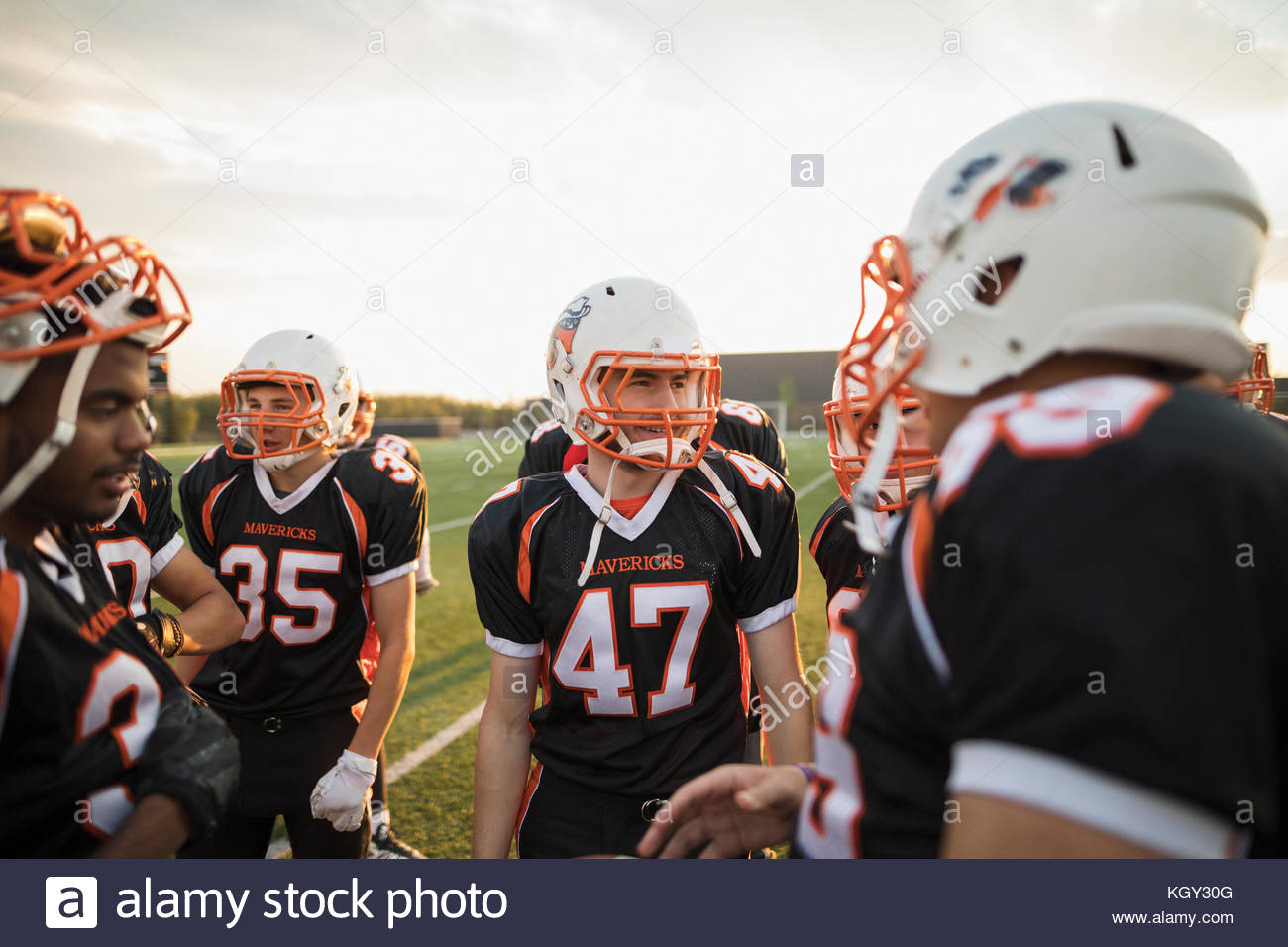 Teenage boy high school l'équipe de football de parler en caucus sur terrain de football Photo Stock