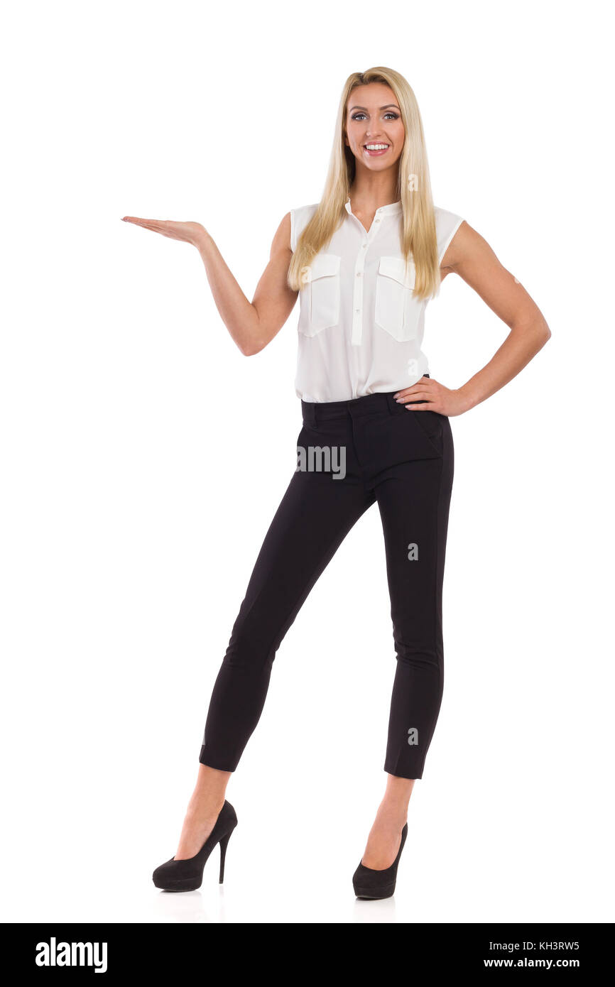79c22feb82bf2 Belle femme blonde en chemise blanche, pantalon noir, et des talons hauts  qui posent avec main levée, présenter, smiling at camera et pleine longueur  stud.