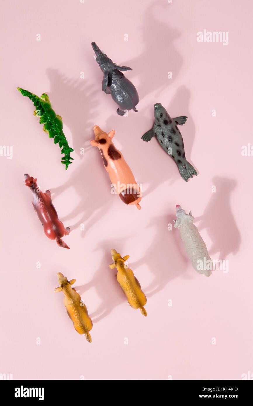 Figurine en plastique différents animaux jouets comme un troupeau sur fond rose vibrant. minimal still life Photo Stock