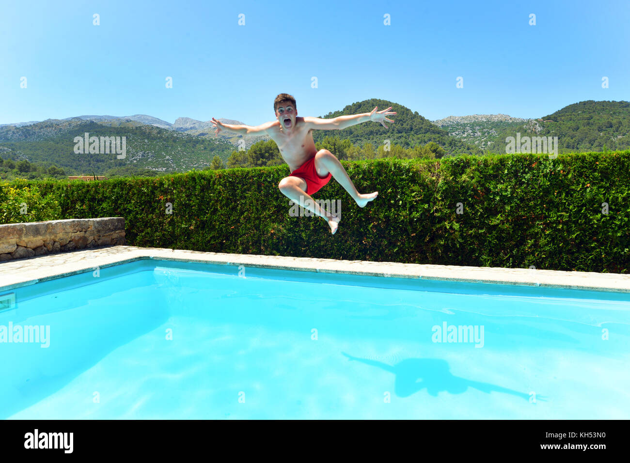 Teenage boy jumping dans une villa privée piscine Photo Stock