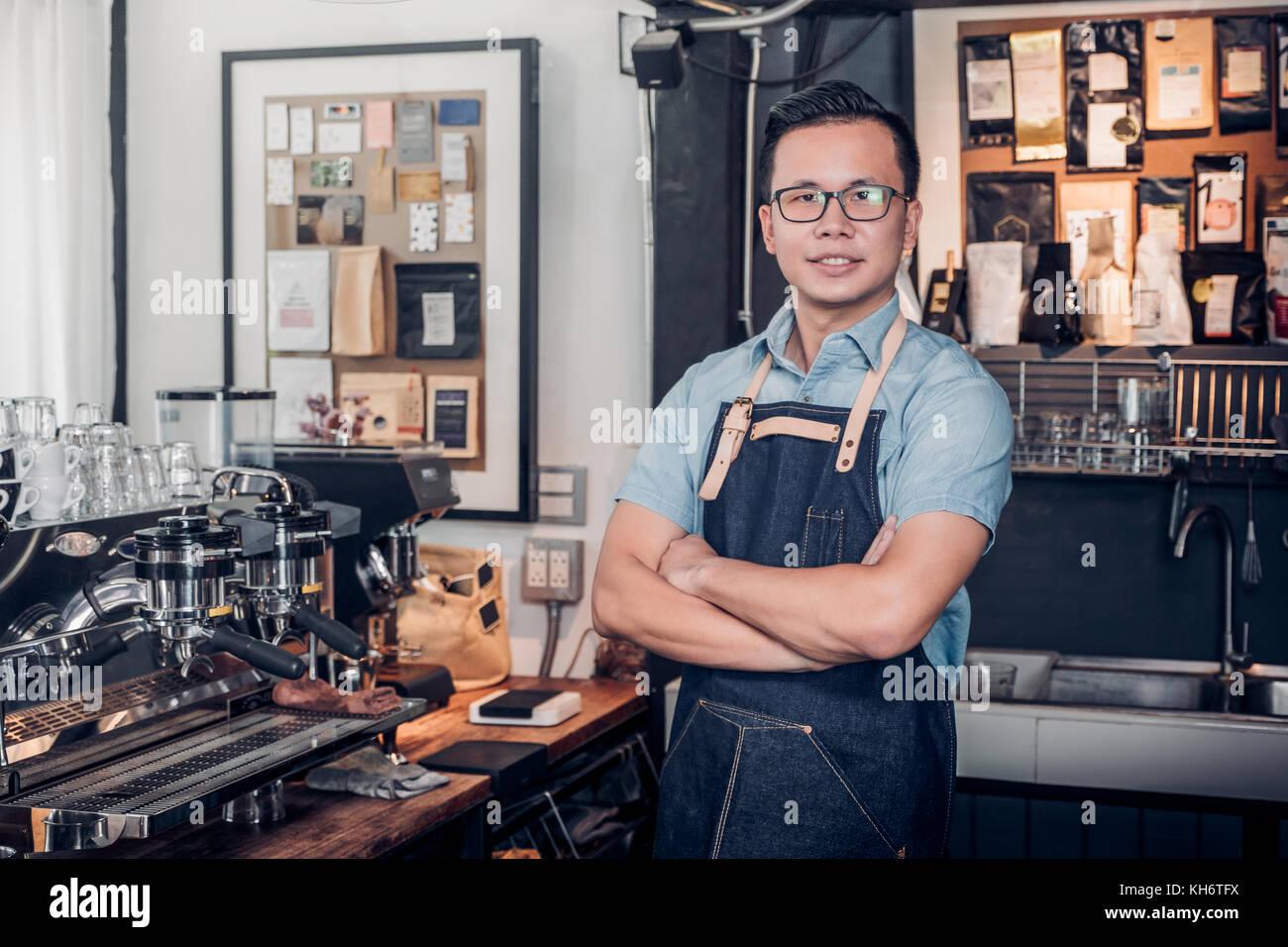 Café barista mâle propriétaire cross arms dans comptoir du magasin bar à l'intérieur d'un café, des boissons et Banque D'Images