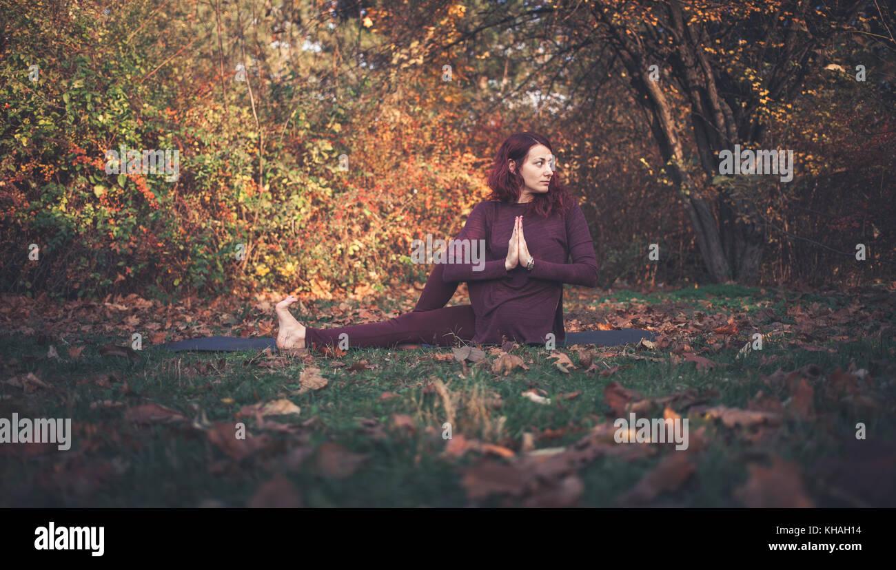 Girl une journée d'automne, la pratique du yoga en plein air, faisant ardha matsyendrasana (demi-seigneur Photo Stock