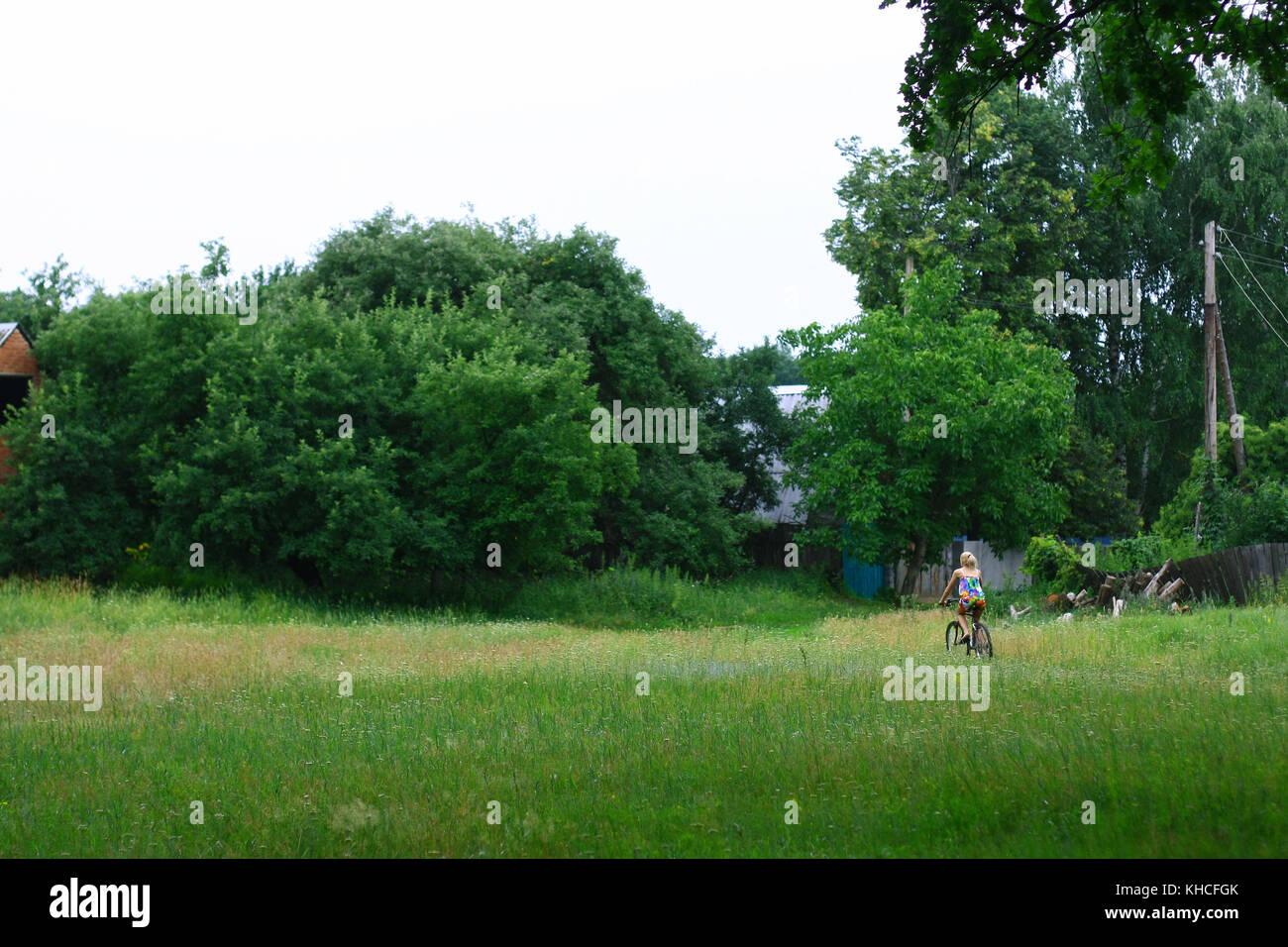 Photo horizontale de belle blonde jeune fille équitation son vélo dans un village Banque D'Images