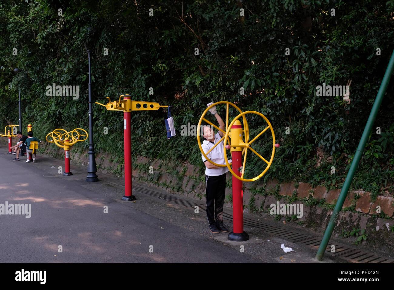Femme à l'aide de l'équipement d'exercice dans le parc municipal de la colline de Guia, Macao, Photo Stock
