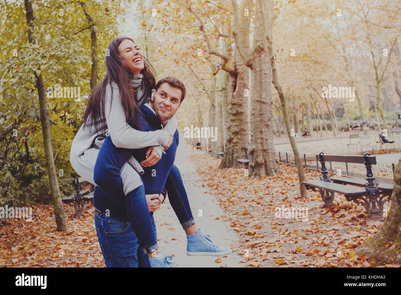 Man carrying woman piggyback, dating, young couple laughing in autumn park Photo Stock