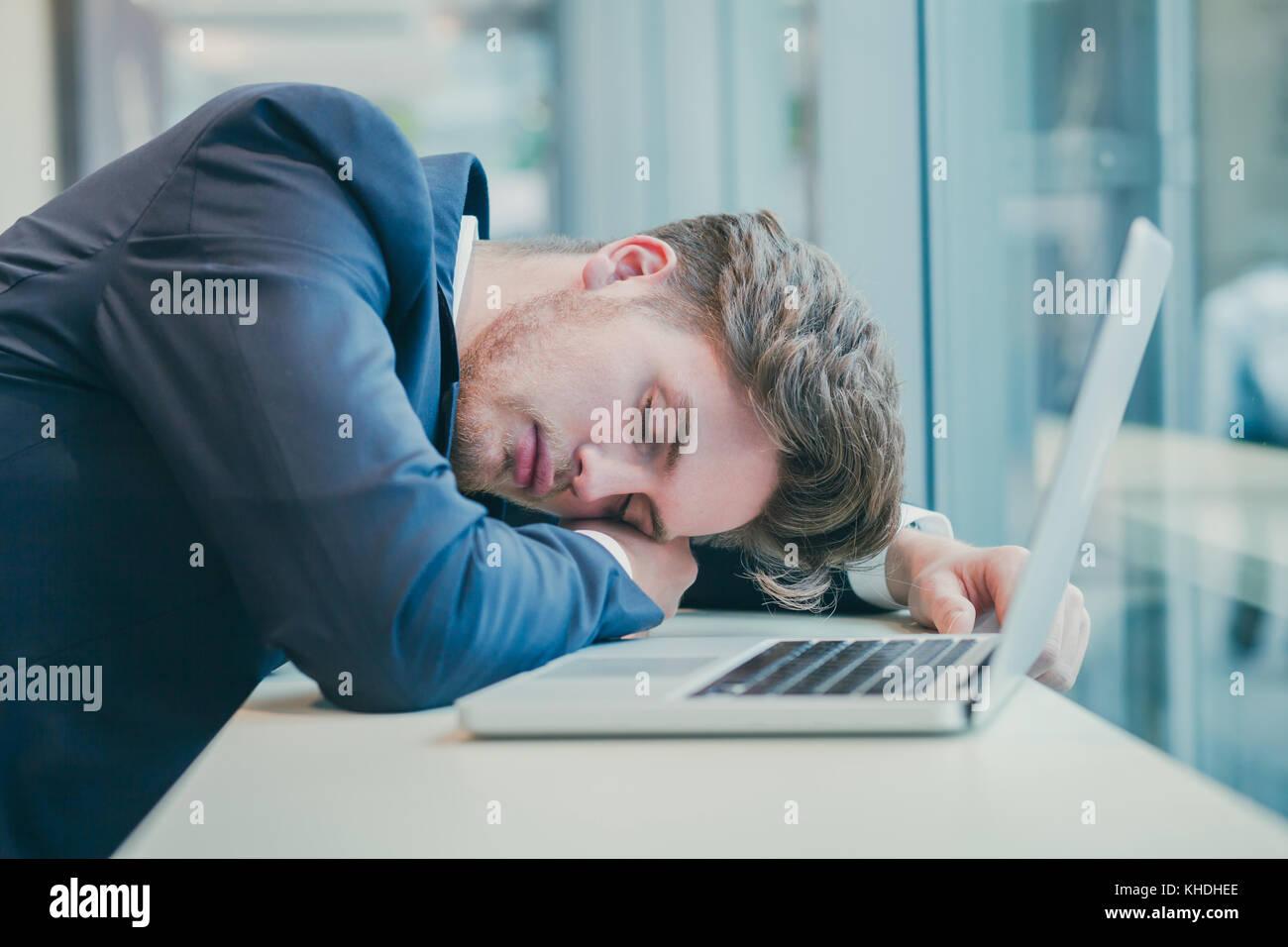 Fatigué businessman sleeping près de l'ordinateur Photo Stock