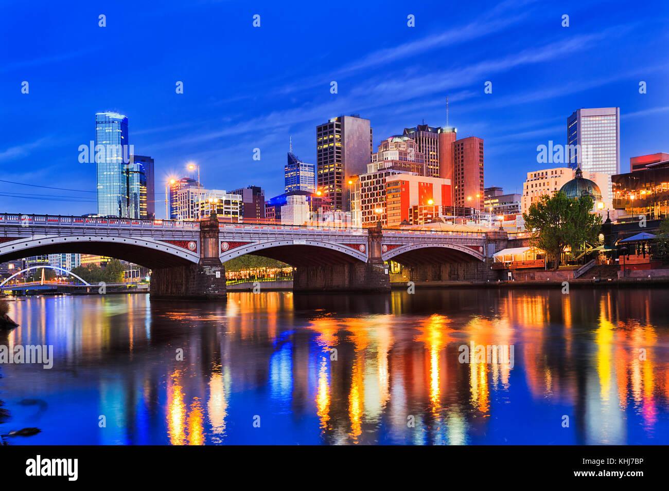 Princes bridge sur la rivière Yarra de Melbourne CBD de la ville au lever du soleil lorsque les éclairages lumineux dans l'eau trouble reflètent. Banque D'Images