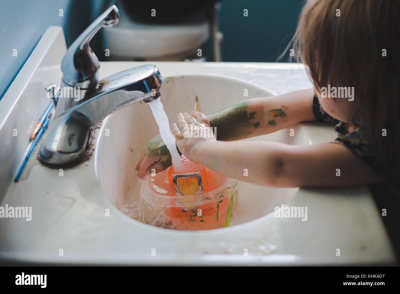 Un bébé fille lave la peinture sur ses mains dans un évier de salle de bains. Banque D'Images