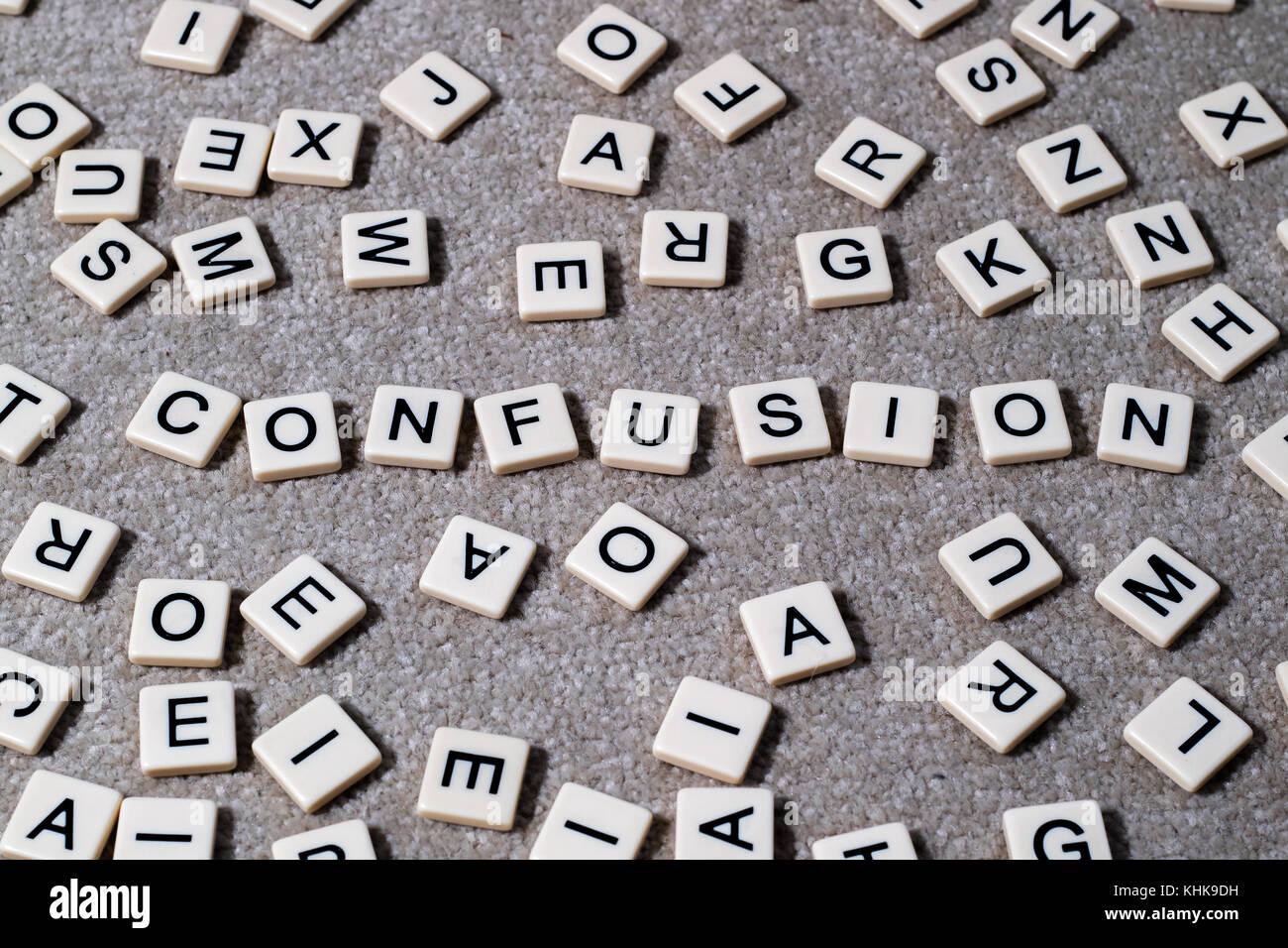 La confusion en toutes lettres sur les tuiles de SCRABBLE lettres style parmi un fatras d'autres lettres. Photo Stock