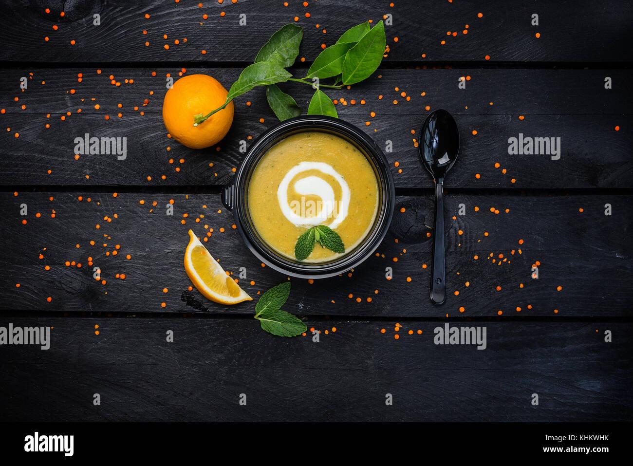 Crème de lentilles avec une cuillère à soupe de citron et noir sur fond de bois foncé. haut voir l'image. Banque D'Images
