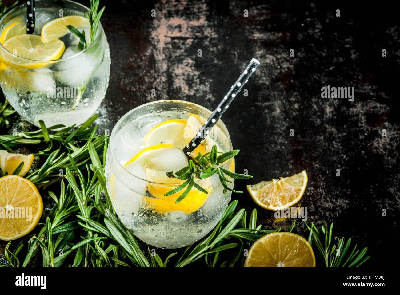 L'alcool froid limonade ou cocktail vodka avec du citron et du romarin, sur un arrière-plan noir métallique Photo Stock