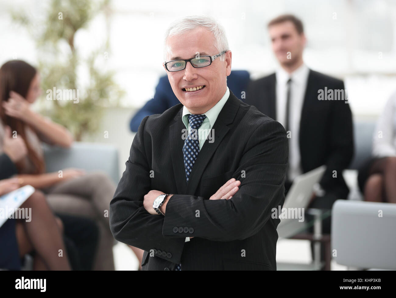 Smiling senior businessman sur le contexte de l'équipe commerciale Photo Stock
