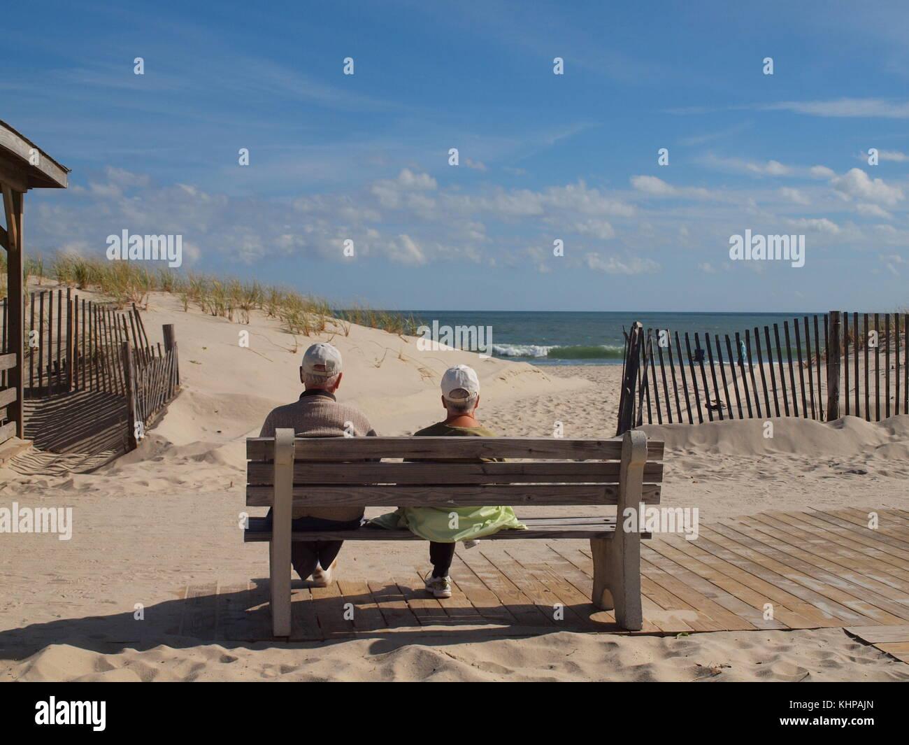 Couple de personnes âgées bénéficiant du soleil sur un banc de la station balnéaire du Photo Stock