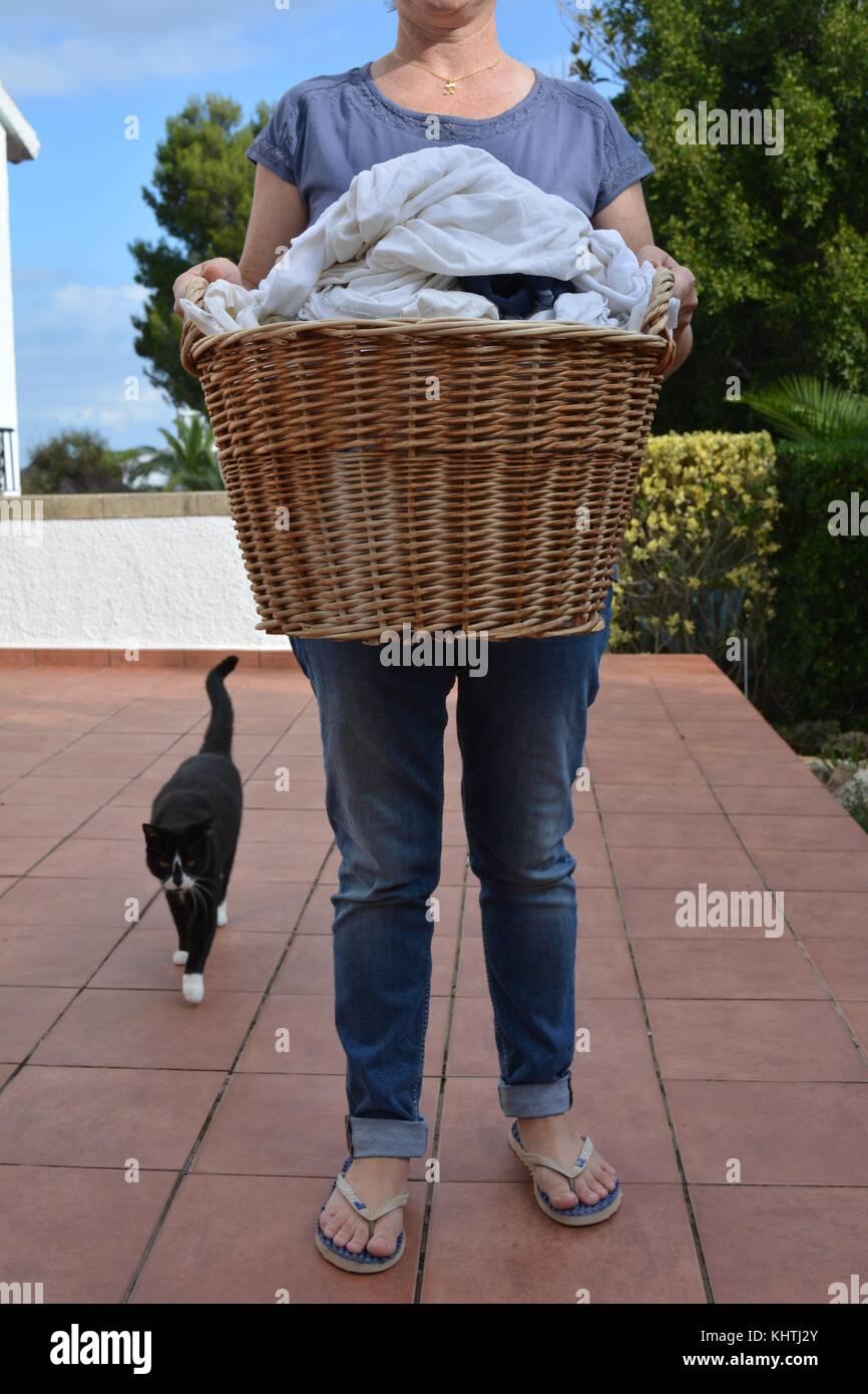 Laundry day. femme transportant un panier en osier le linge humide pour être suspendus pour sécher, suivi Photo Stock