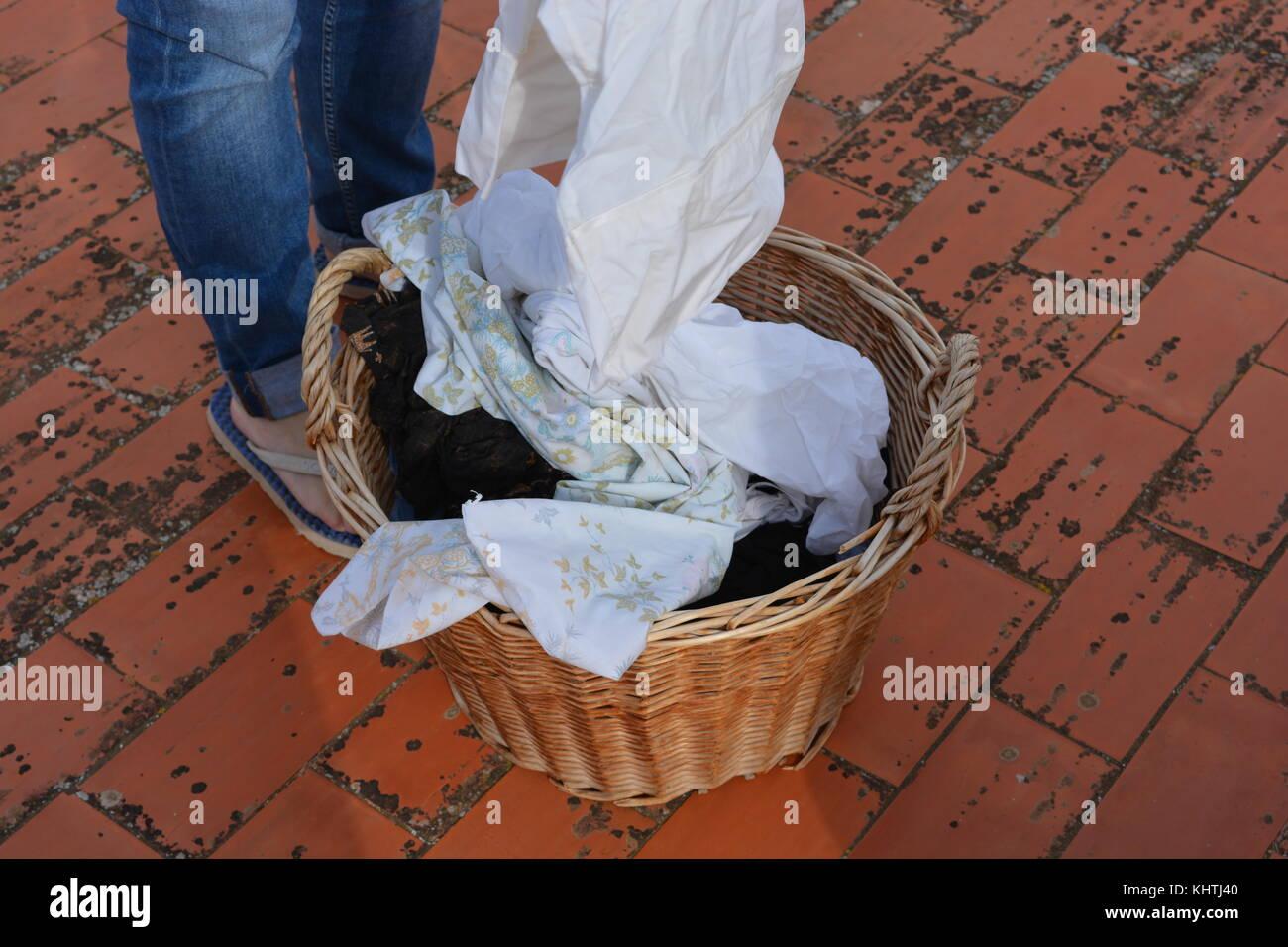 Laundry day. femme avec un panier en osier de pendre le linge humide pour sécher, suivi d'un chat Photo Stock