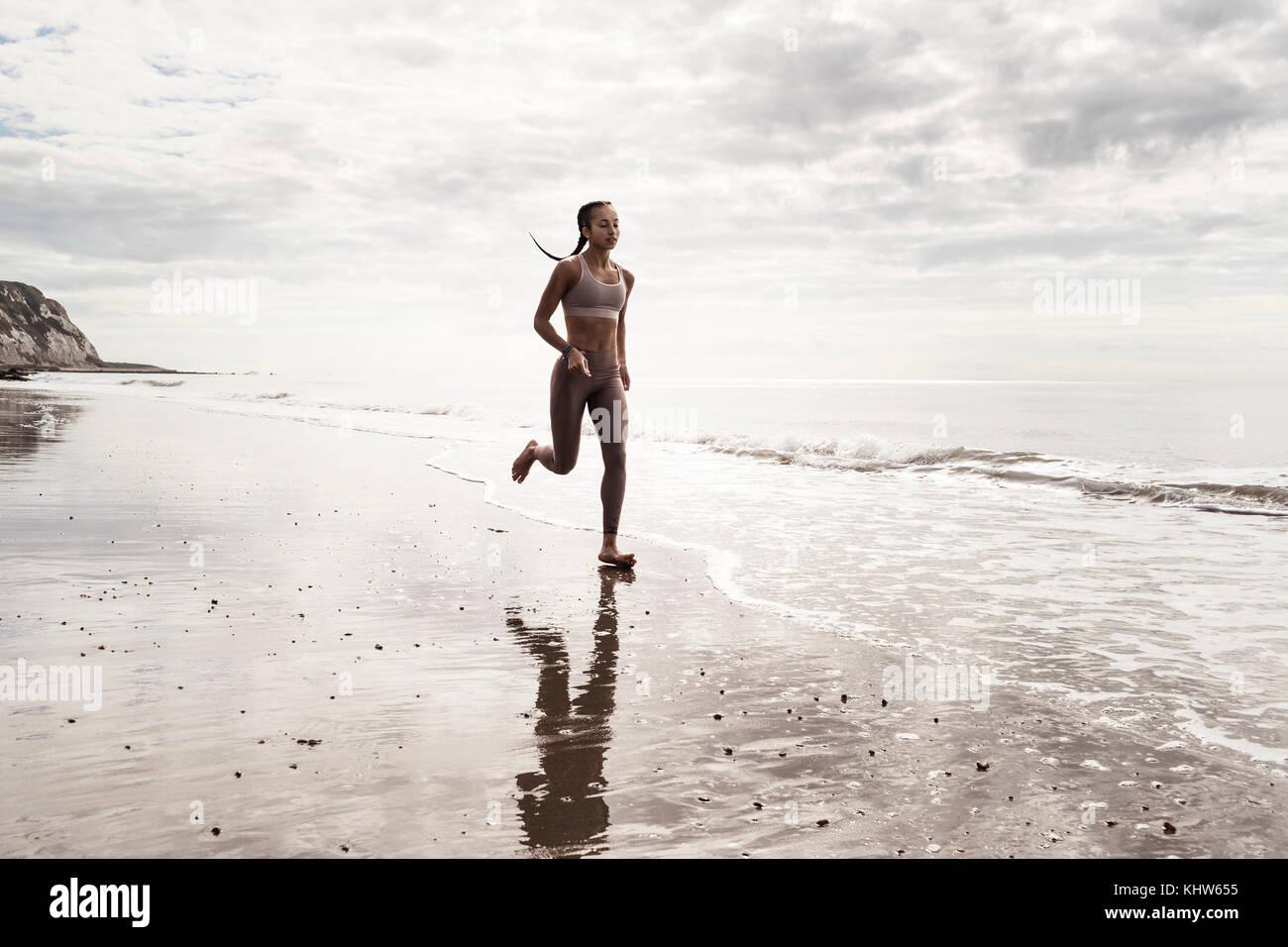 Jeune coureuse en marche pieds nus le long de la plage au bord de l'eau Photo Stock