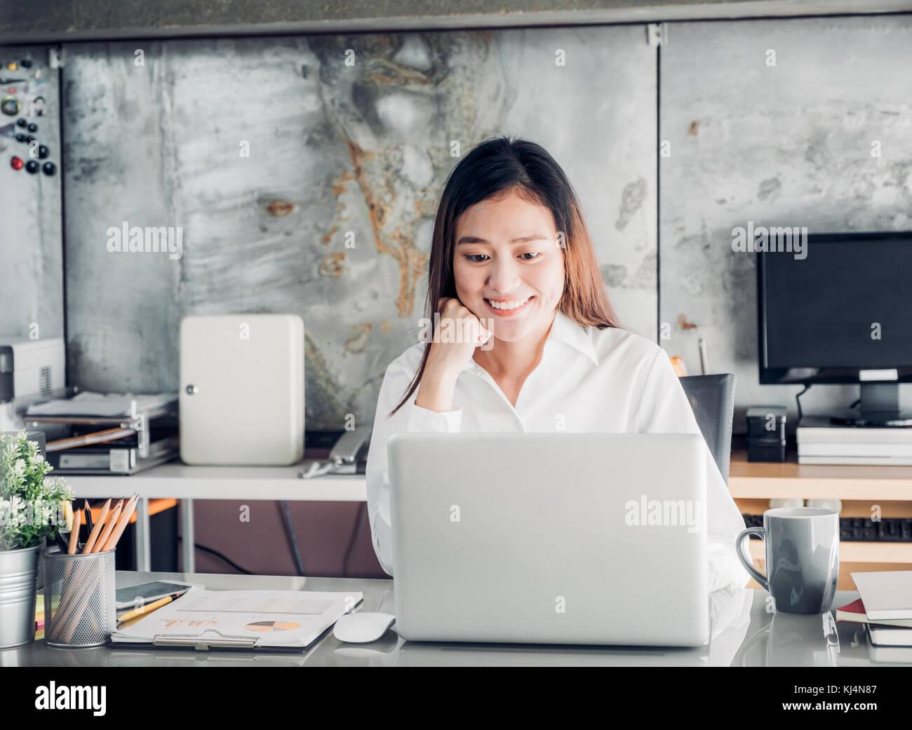 Asie businesswoman looking at laptop computer et visage souriant et de repos avec des professionnels de l'émotion Banque D'Images