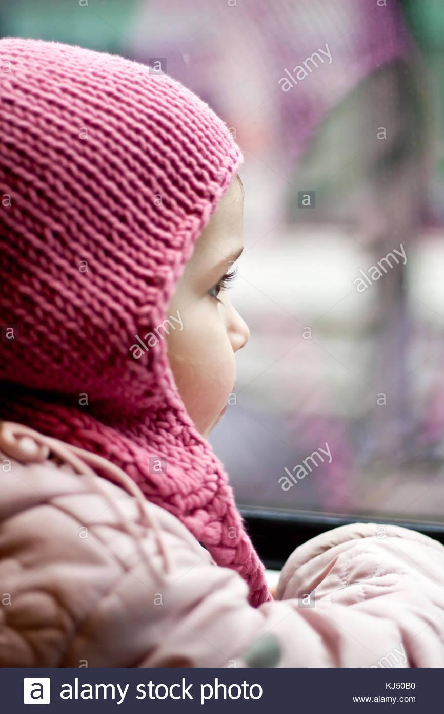 Little girl in a pink hat tricoté en regardant par la fenêtre Photo Stock