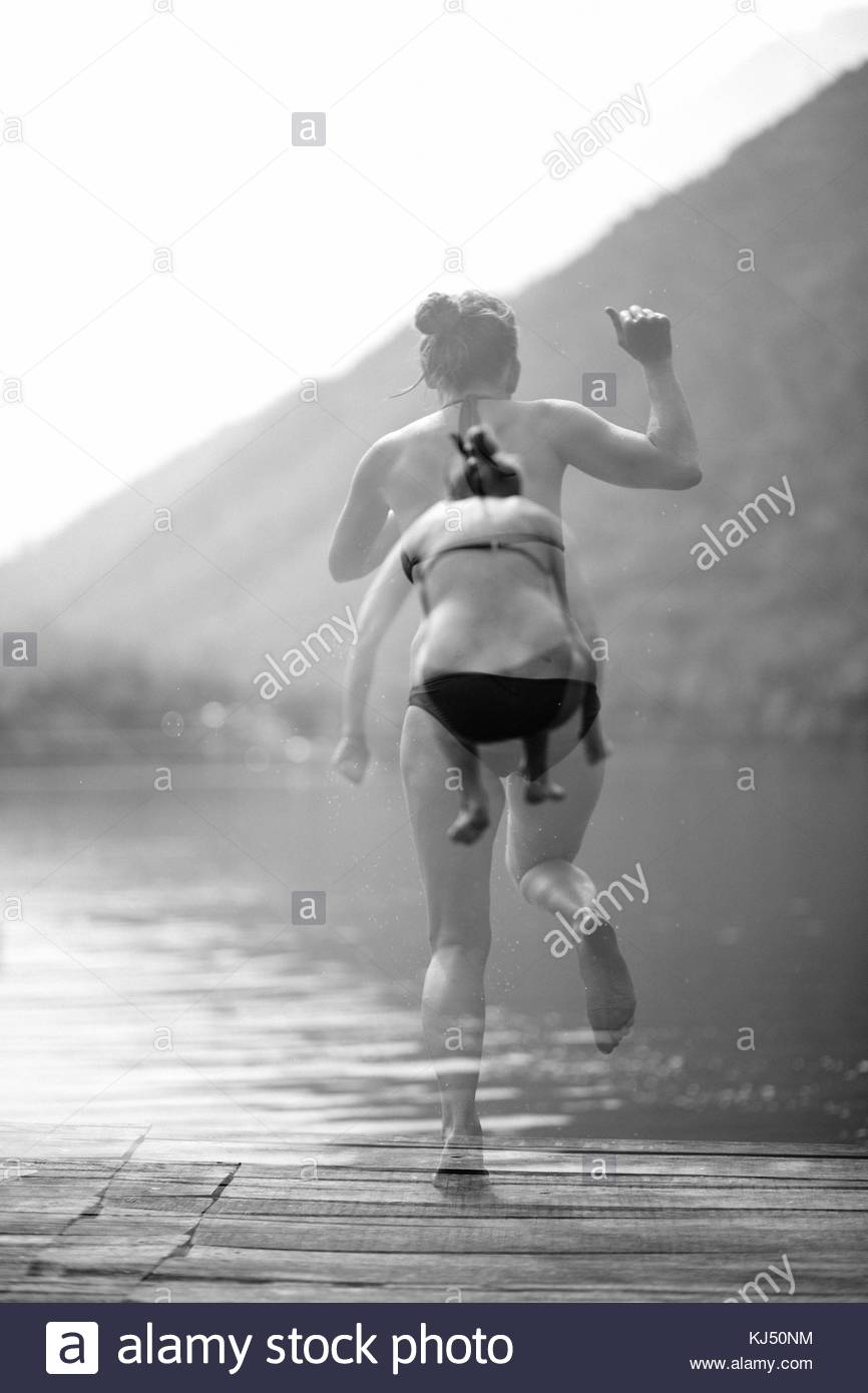 Double exposition de jeune fille sautant dans l'eau Photo Stock