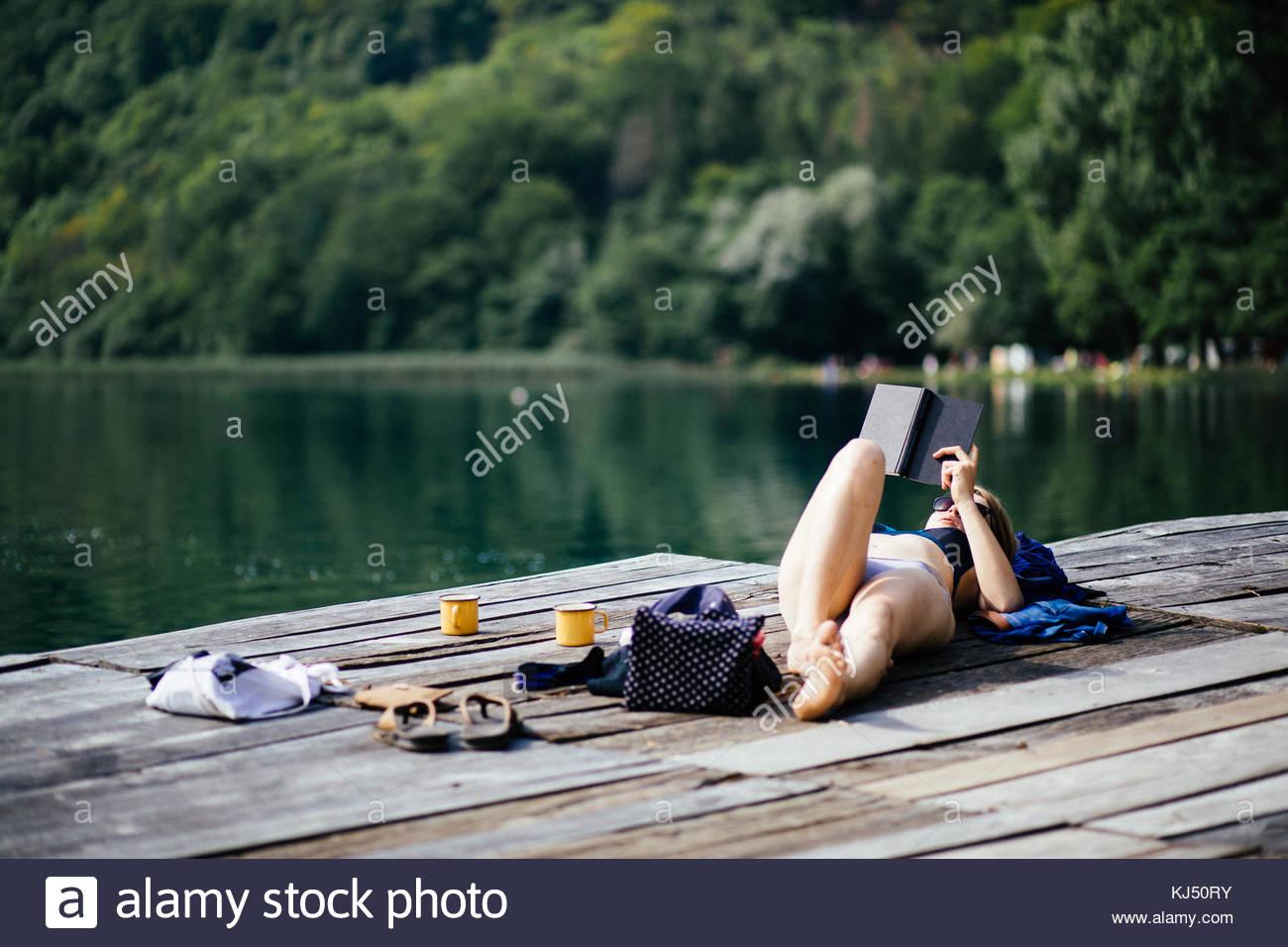 Young woman in bikini portant la lecture d'un livre sur une jetée en bois Photo Stock