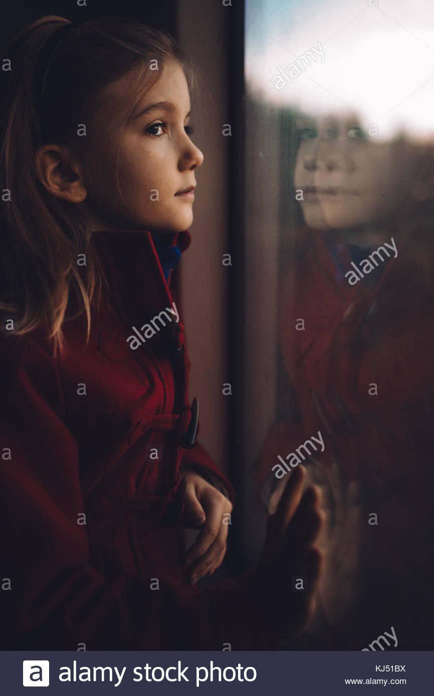 Petite fille en regardant par la fenêtre Photo Stock