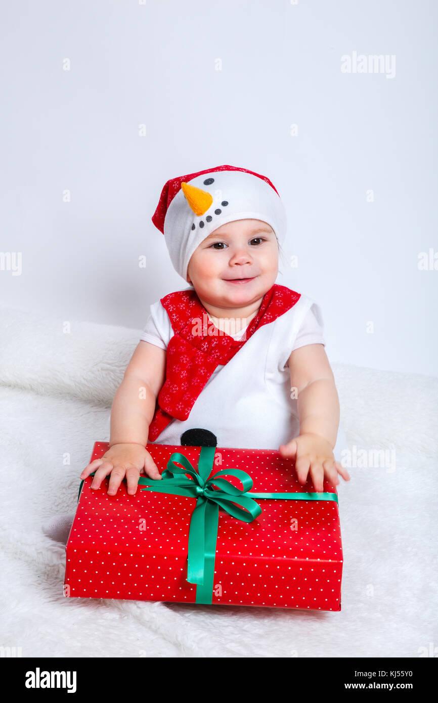 df3ea34567073 Heureux bébé en costume de Noël Bonhomme de neige avec cadeaux Ticket Photo  Stock