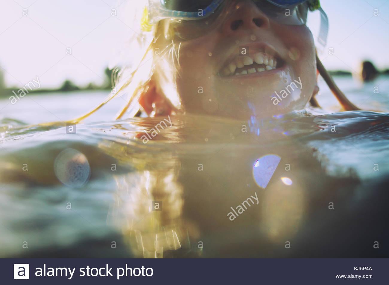 Heureux l'enfant nage avec lunettes de natation Photo Stock
