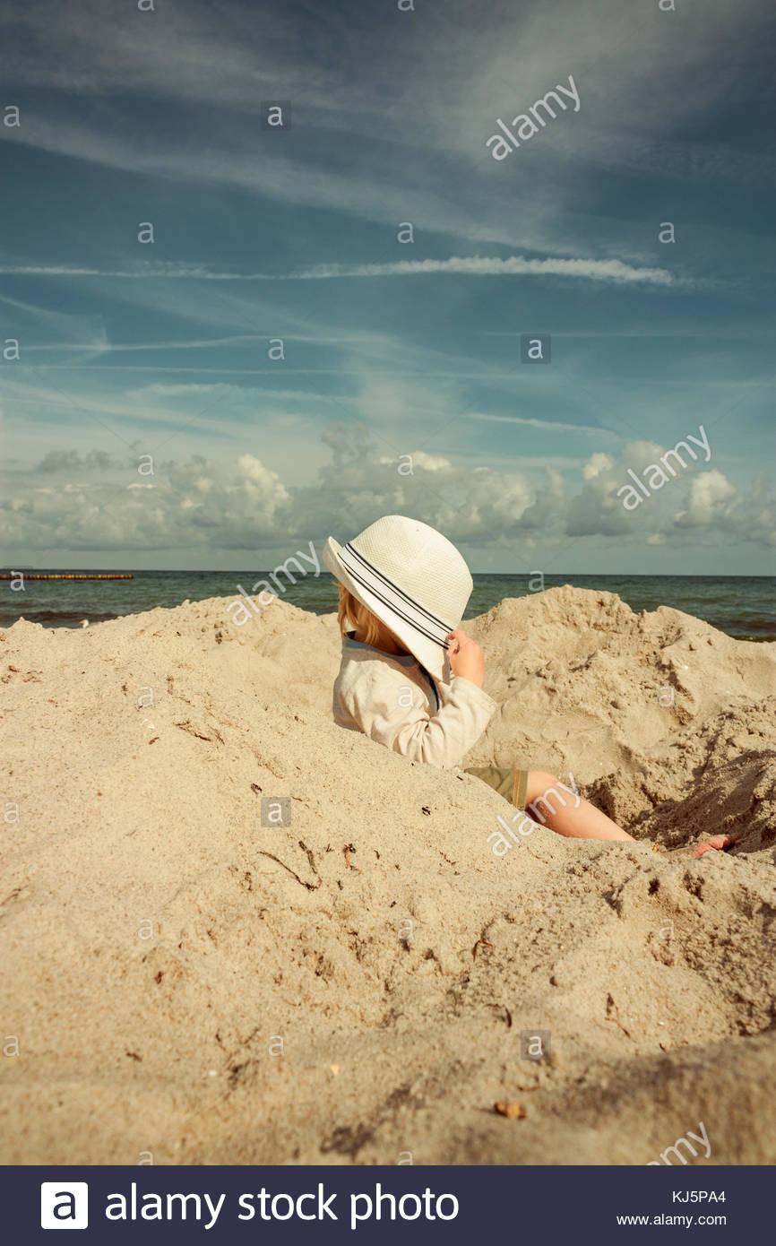 Enfant assis dans un trou sur la plage, le visage couvert par un chapeau Photo Stock