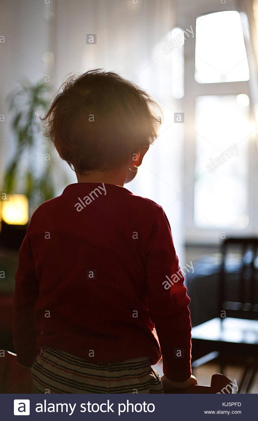 Jeune enfant assis près de la vue arrière de la fenêtre Photo Stock