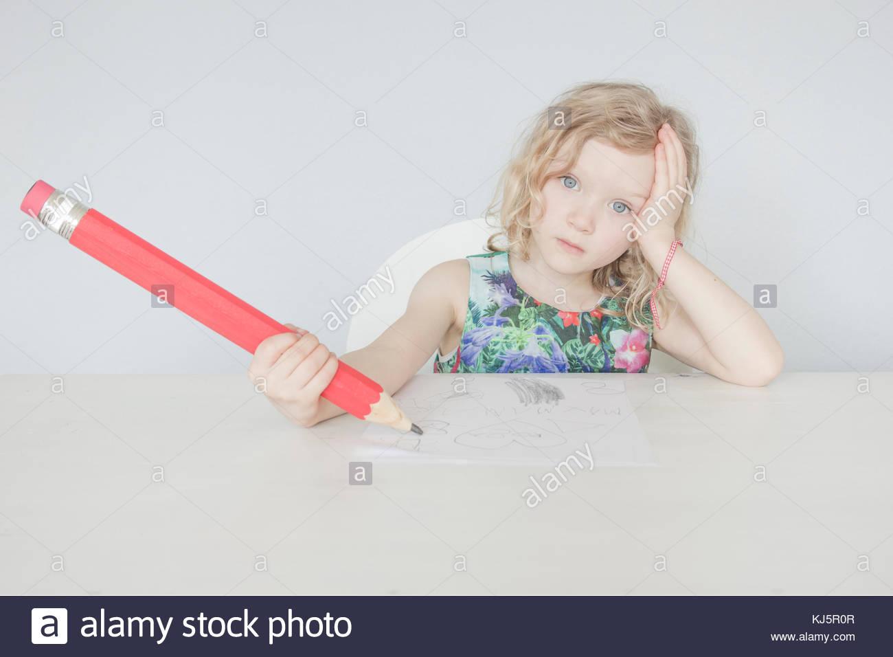 Belle blonde petite fille écrit avec un gros stylo Photo Stock