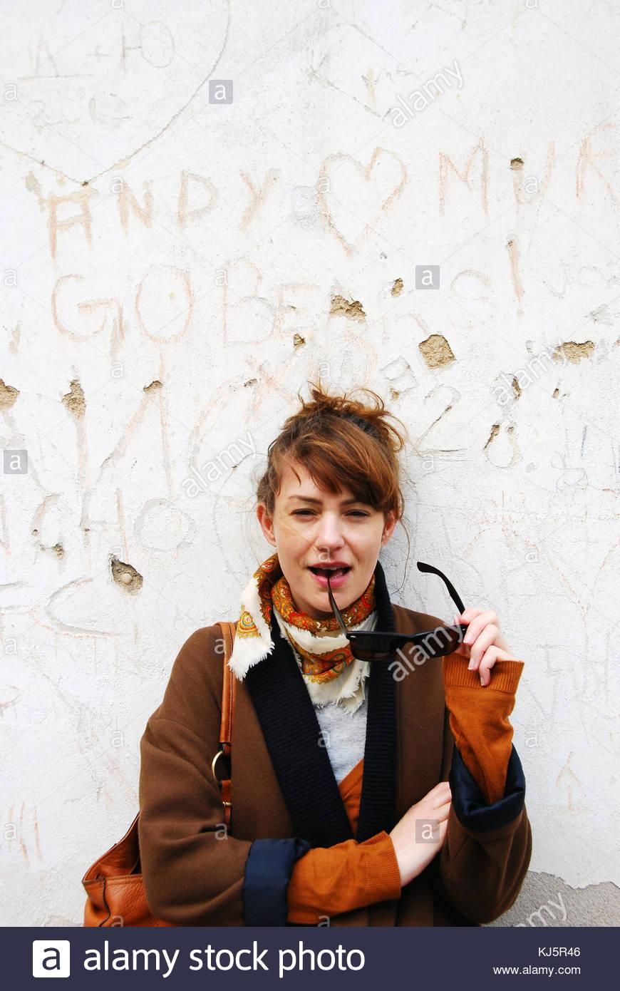 Jeune femme avec des lunettes de soleil par mur gravé blanc Photo Stock