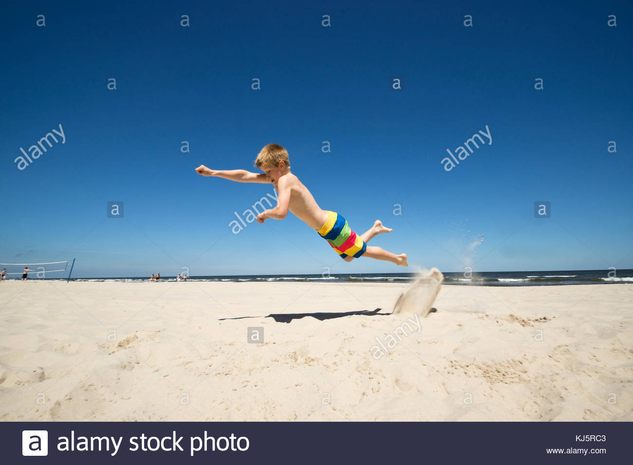 Jeune garçon sautant sur le sable Photo Stock