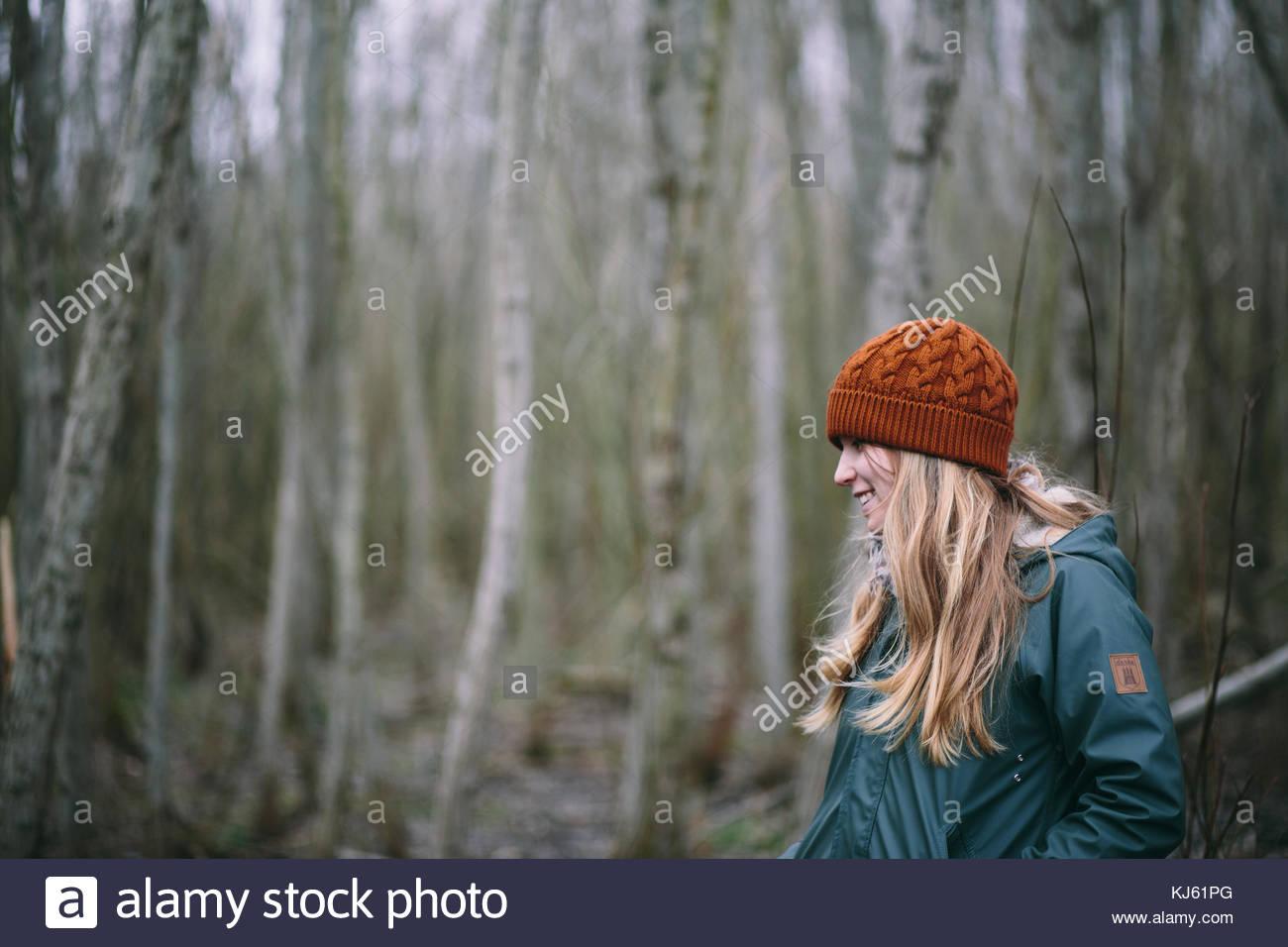 Fille blonde avec brown hat tricoté en forêt Photo Stock