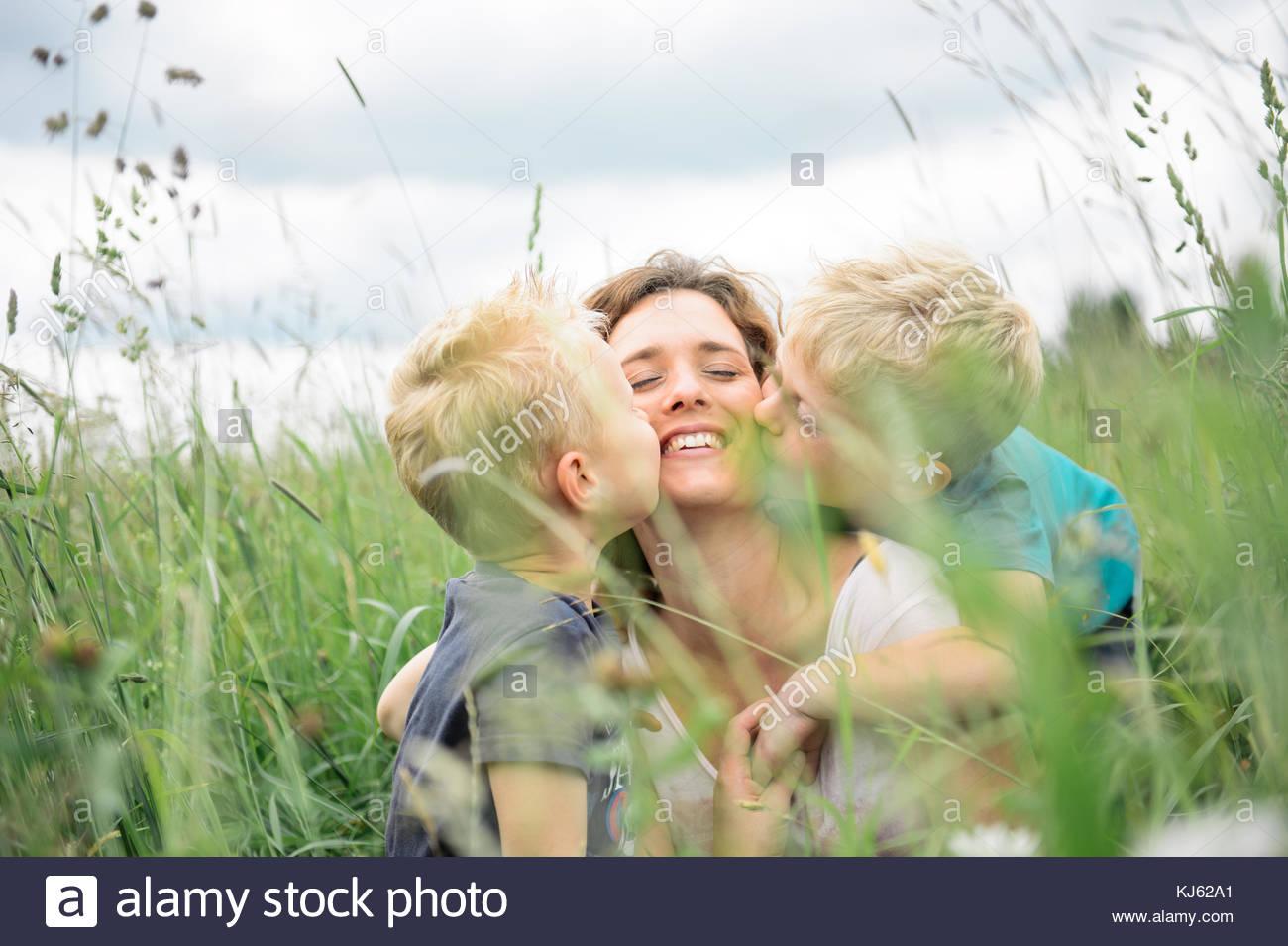 Mère embrassant leurs enfants dans un pré Photo Stock