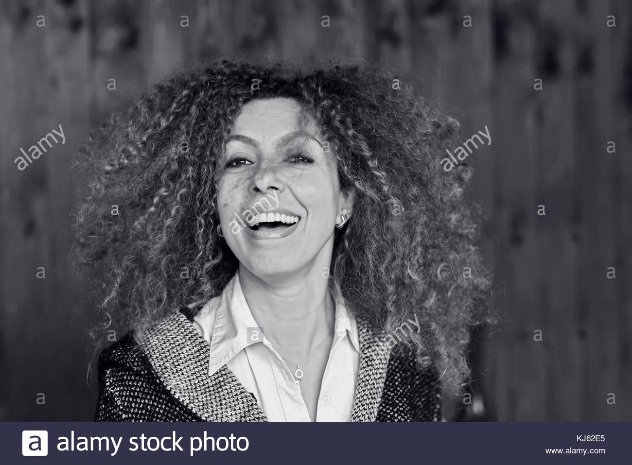 Femme d'âge moyen aux cheveux bouclés de profiter de la vie Photo Stock