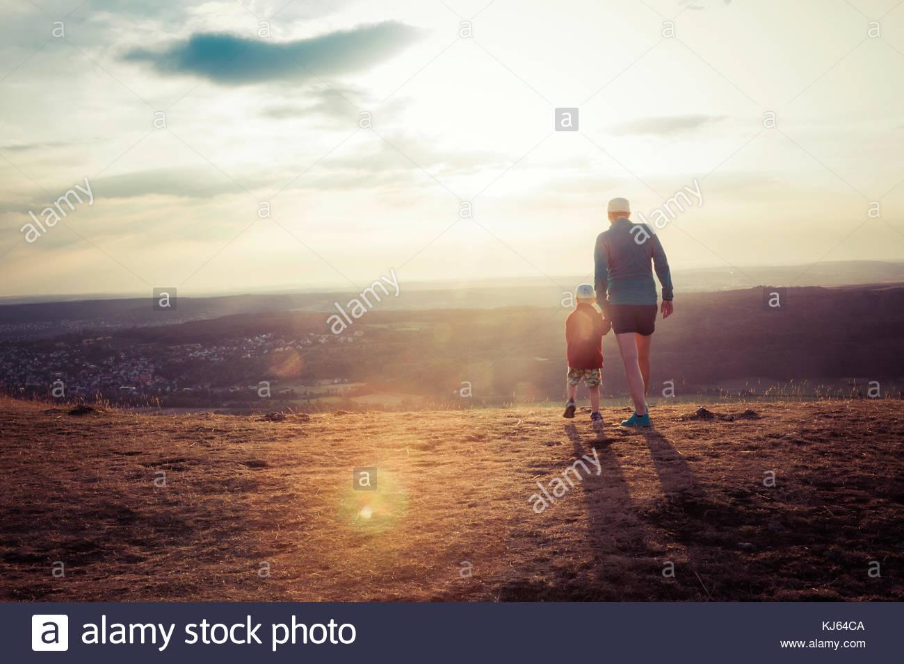 Père et fils à pied les collines dans la lumière au coucher du soleil se retourna. Photo Stock