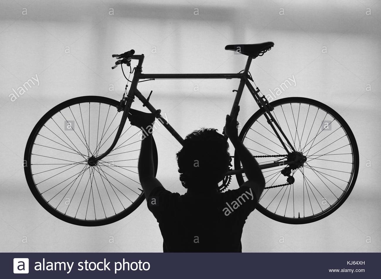 Silhouette of man holding un vélo Photo Stock