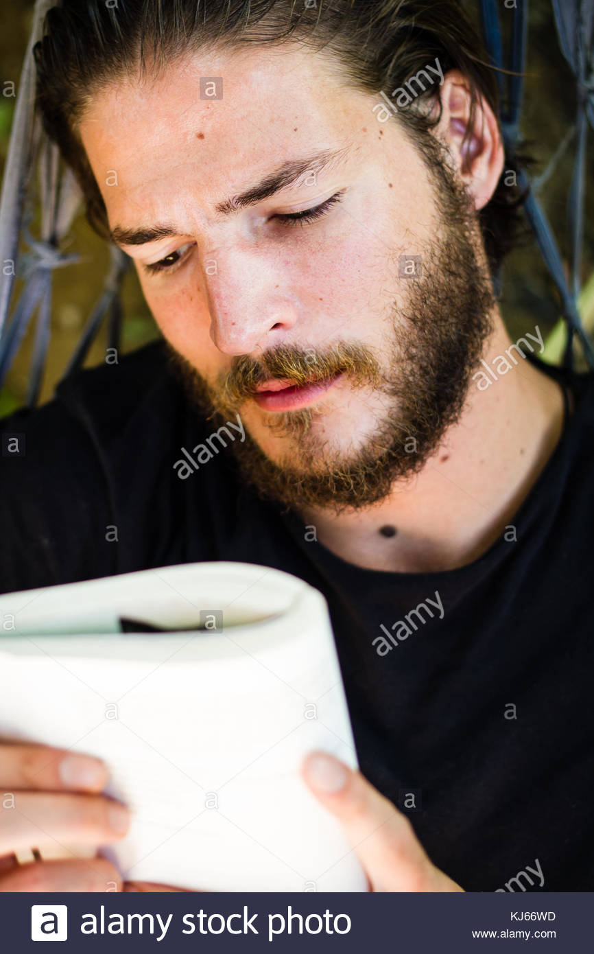 Young man reading book Photo Stock