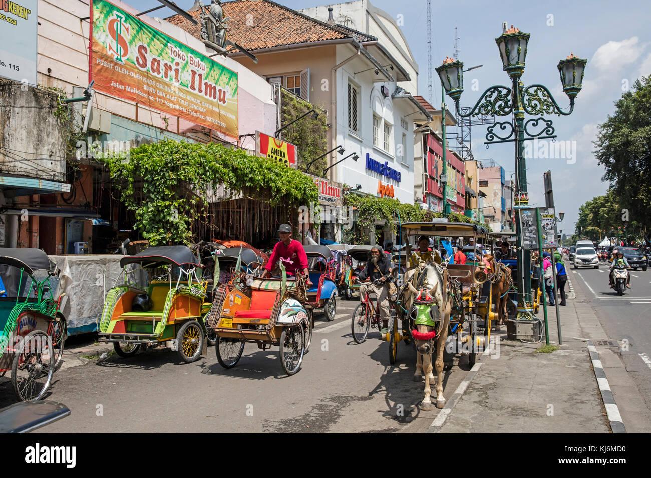 Vélos-pousse / becak et calèches pour les transports publics à Jalan Malioboro, principale rue commerçante à Yogyakarta, java, Indonésie Banque D'Images