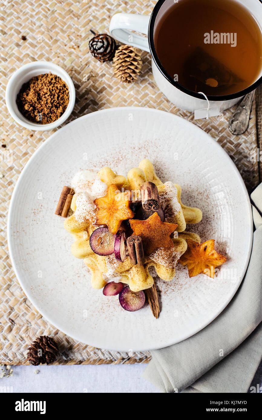 Table du petit déjeuner: gaufre avec des fruits, de la cannelle et du yaourt. Vue de dessus le temps Photo Stock