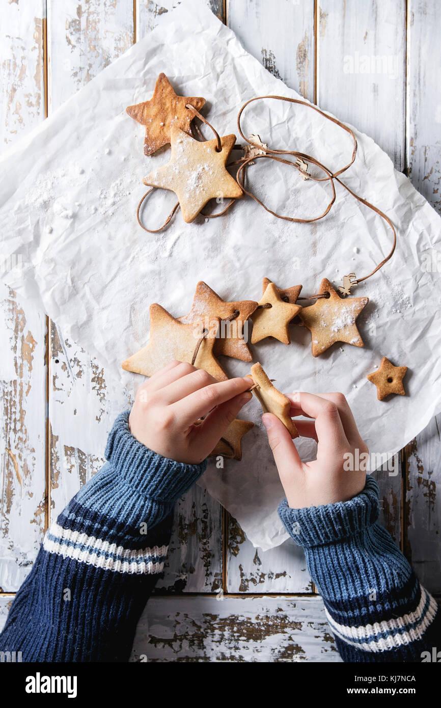 Les mains de l'enfant faire des sablés faite guirlande de star shape sugar cookies autre taille sur le thread sur Banque D'Images