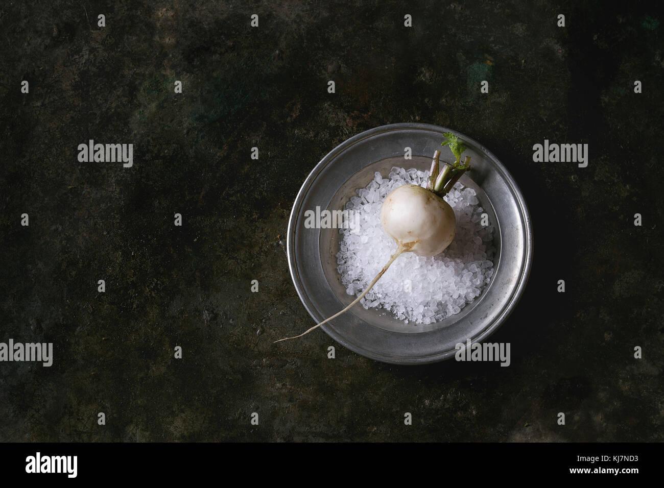 Ensemble blanc frais radis biologiques dans la plaque de métal avec du sel de mer sur dark metal texture background. Photo Stock