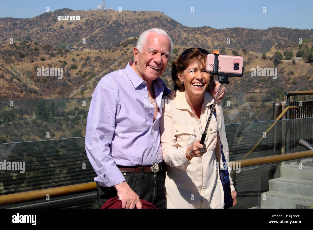 Couple avec stick selfies en prenant des photos avec un téléphone cellulaire et panneau Hollywood à Photo Stock