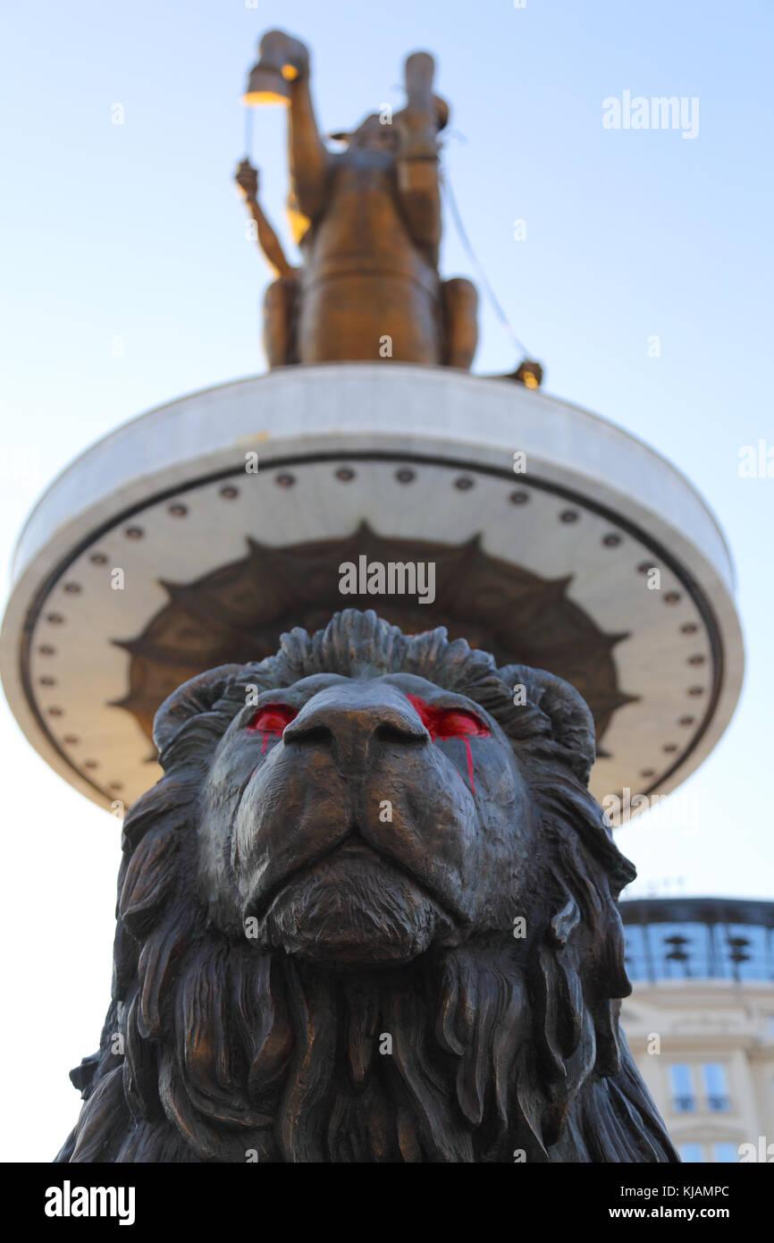 La figure d'un lion à la base du monument guerrier sur un cheval avec les yeux peints en rouge à Skopje, Photo Stock
