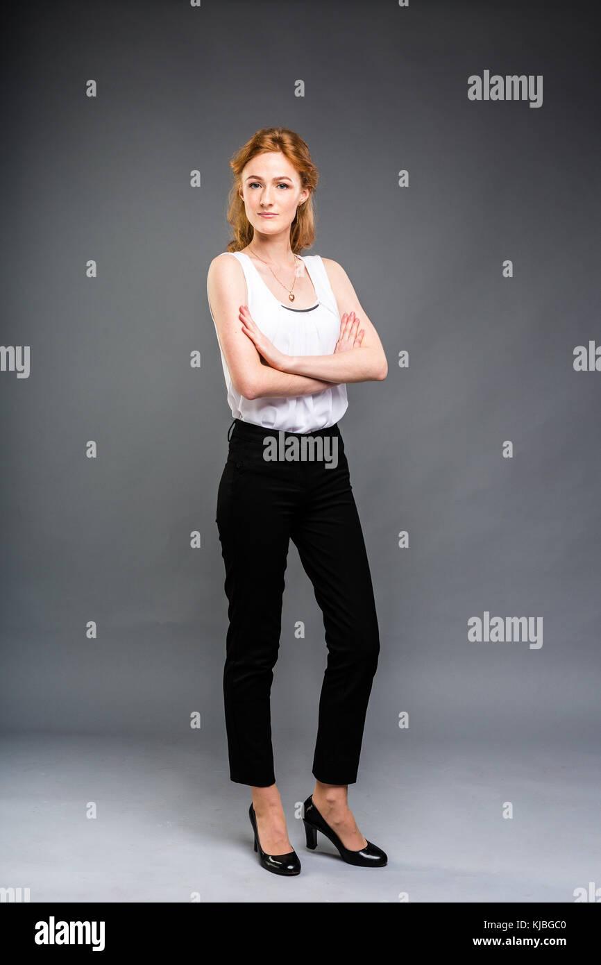 Belle jeune femme de race blanche avec de longs cheveux rouges à hauts talons, un pantalon noir et une chemise blanche Banque D'Images