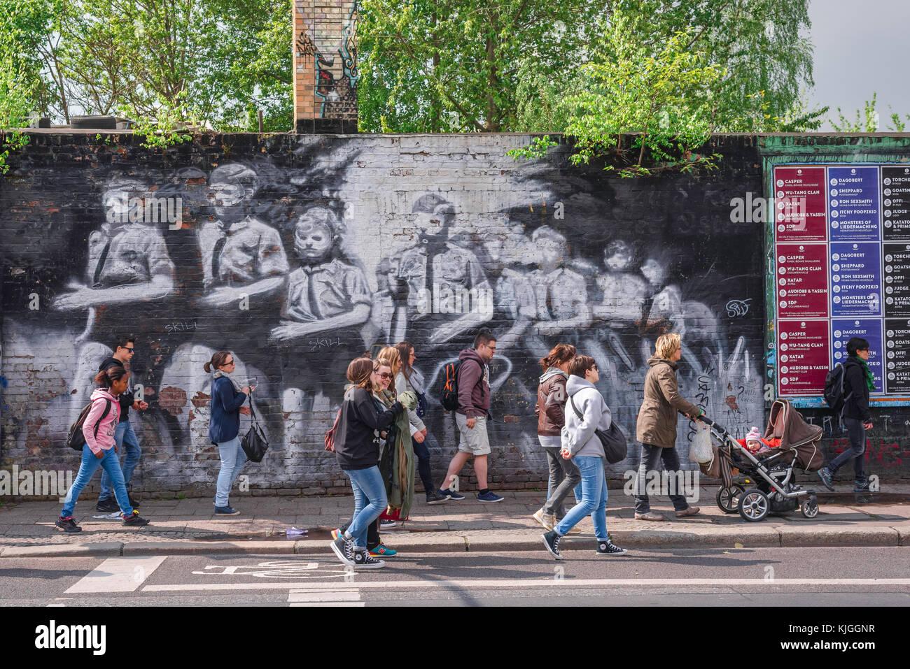 Mur de Berlin, les gens devant une peinture murale représentant la jeunesse hitlérienne peint sur le mur Photo Stock