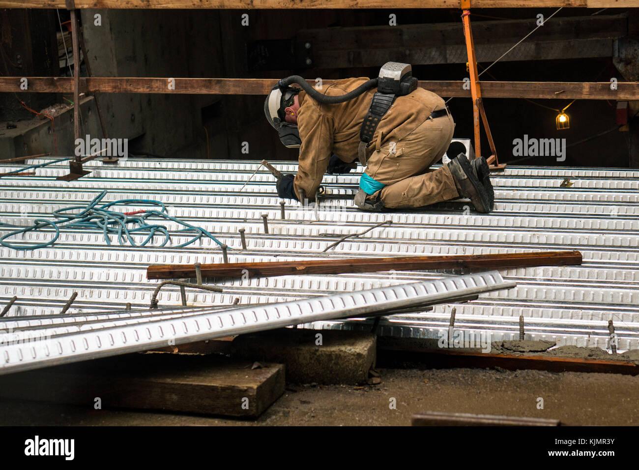 Un homme sur les genoux de soudure de la tôle tout en portant un casque de  protection, masque de protection respiratoire, et fait son travail sur un  ... a8cf4c0b8900