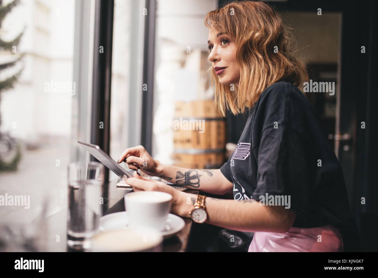 Pretty girl smiling et regardant par la fenêtre d'un bar Photo Stock